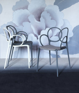 two driade design chairs ahead a wallpaper decorated wall