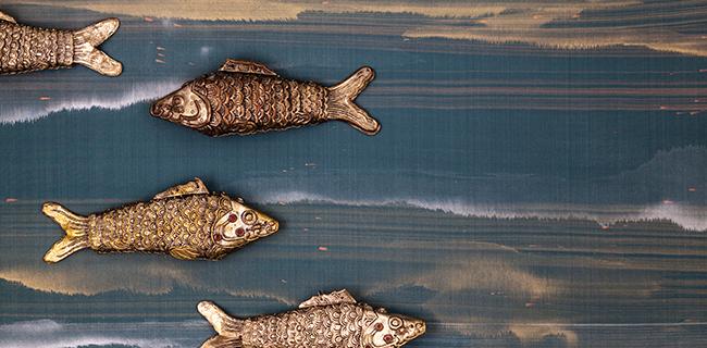 Pesci metallici appoggiati su tessuto a parati