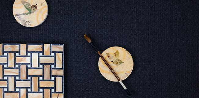 Tessuto da parati blu con appoggiati piatti e un pennello
