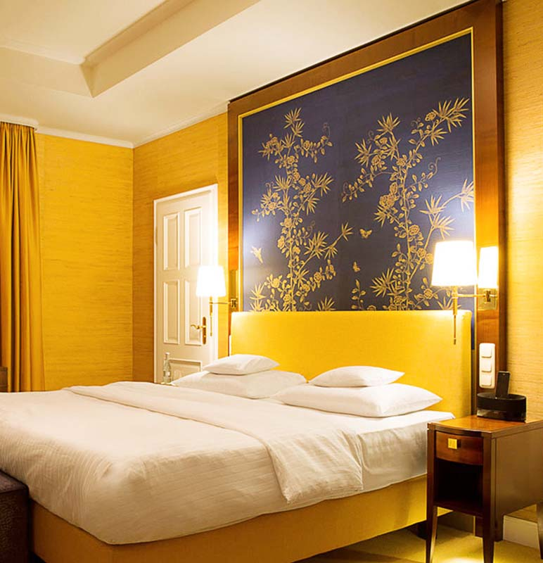 kempiski hotel bedroom with silk chinoiserie wallpaper gold bamboo garden